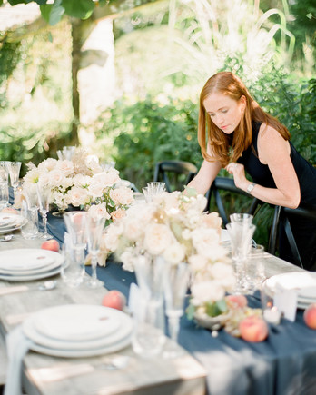 wedding planner putting finishing touches on a reception table