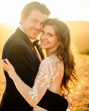 bride and groom hold each other smiling on california hillside