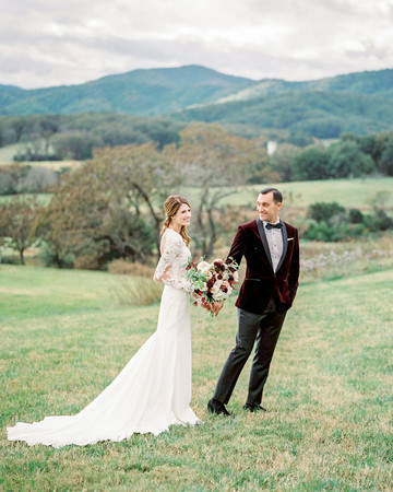 bride and groom stand on grassy hillside outdoors