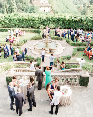 wedding guests gather outside for cocktail hour