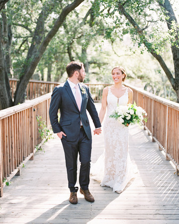 lauren aaron wedding couple holding hands on bridge