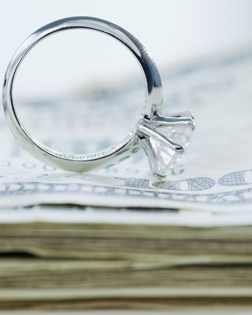 engagement ring sitting on money