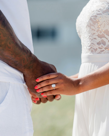 couple holding hands displaying engagement ring