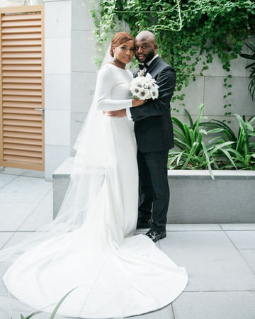 vanessa abidemi wedding couple in front of building and greenery