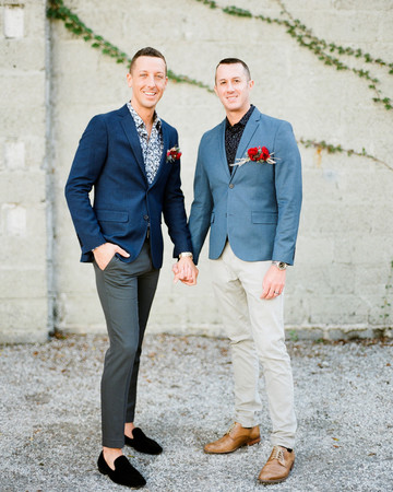 grooms wearing blue gray accented wedding suits with red boutonnieres