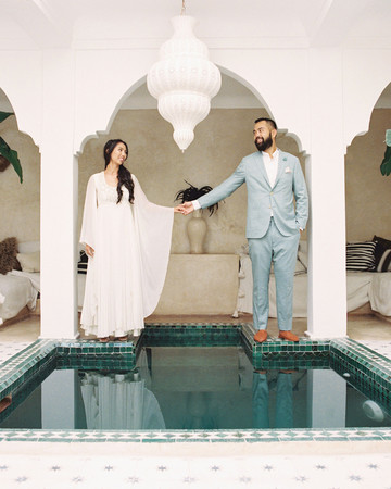 bride and groom stand next to small pool in moroccan styled building