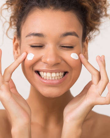 Happy Young Woman Applying Skincare Products