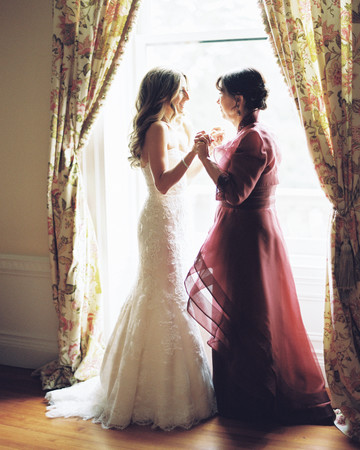 A Bride and Her Mom Holding Hands Before the Wedding