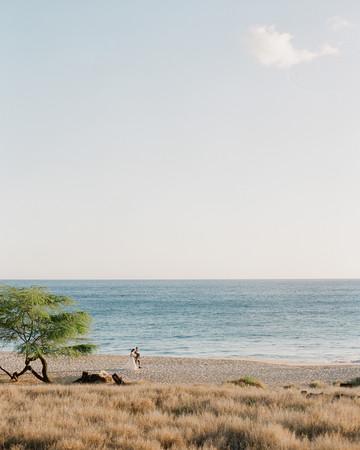 bride and groom hawaiian beach ocean front walk