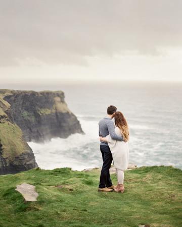 destination engagement couple ocean view over rock cliff