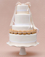 Four-Tiered White Wedding Cake with Ribbon and Ringed Maracons