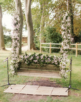 wooden bench swing covered with flowers and greenery