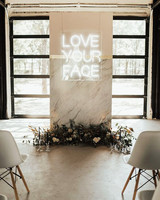 love your face neon sign behind ceremony alter