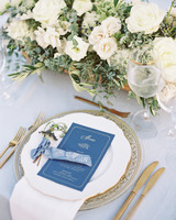 white and gold placesettings with dark blue cardstock menus