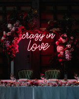 crazy in love neon sign on arch behind head table