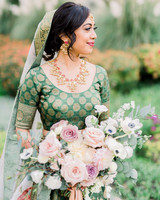 bride holding bouquet in garden outside