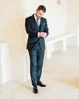 groom wearing dark blue wedding suit and black dress shoes