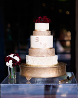 five tiered white and gold decorated wedding cake with rose topper