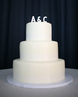 Simple Three-Tiered White Wedding Cake with White Initials Topper
