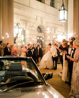 bride and groom kiss under sparkler arch held by guests