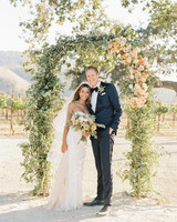 bride and groom outside under olive branch and roses wedding ceremony arch