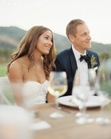 bride and groom sit at reception table during wedding toasts