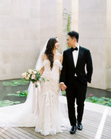 bride and groom holding hands outside next to water