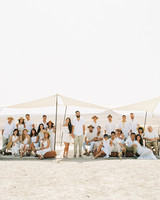 bride and groom with guests under white tent in the desert