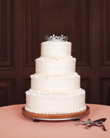 Four-Tiered White Wedding Cake with Silver Paper Crown Topper