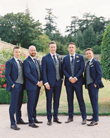 groom and groomsmen wearing dark navy tuxedos with gray checkered vests