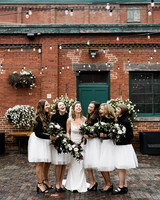 bride with bridesmaids wearing white tulle skirts and black turtlenecks