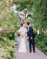 bride and groom walking on outdoor pathway