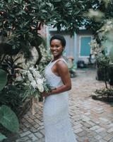 bride wearing beaded gown posing amongst greenery