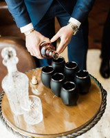 groom pouring shots of scotch whiskey for toast