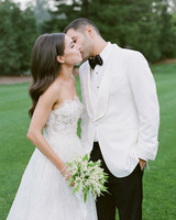 groom kisses bride outdoors in white wedding attire