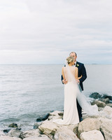 beach wedding dresses couple standing on rocks by the water