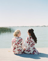 women sitting in robes on dock