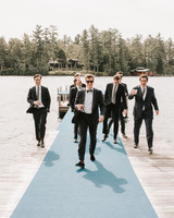 groom with groomsmen walking down lake doc