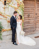 bride and groom looking at each other next to vine covered wall