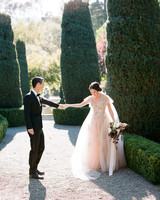 bride and groom share first look in garden area surrounded by shrubs
