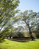 wooden seating outside on grass between trees for ceremony