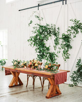sweetheart table wooden with green leaf accented back drop