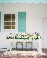 sweetheart table outdoor blue awning floral arrangements and flower petals