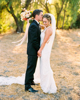 groom kissing brides forehead outdoors