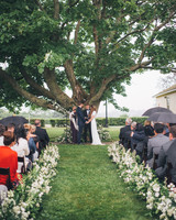 outdoor wedding ceremony below tree guests holding umbrellas