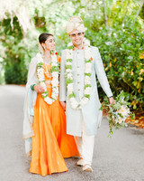 anuja nikhil wedding ceremony couple walking bride orange dress