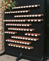 escort cards on copper shelving and black backdrop display
