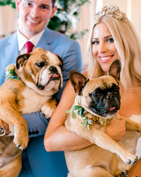 bride and groom holding their bulldogs