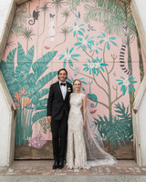 bride and groom pose in wedding attire in front of painted wall