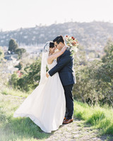 bride and groom face each other on green hillside
